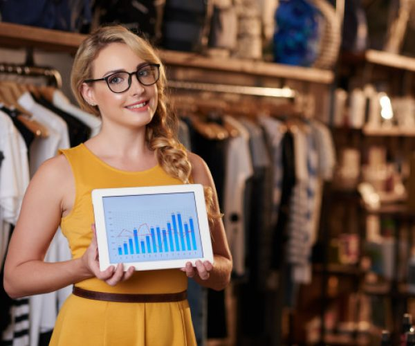 jovem-mulher-caucasiana-em-pe-na-loja-boutique-e-mostrando-o-tablet-com-grafico-de-negocios_1098-20657